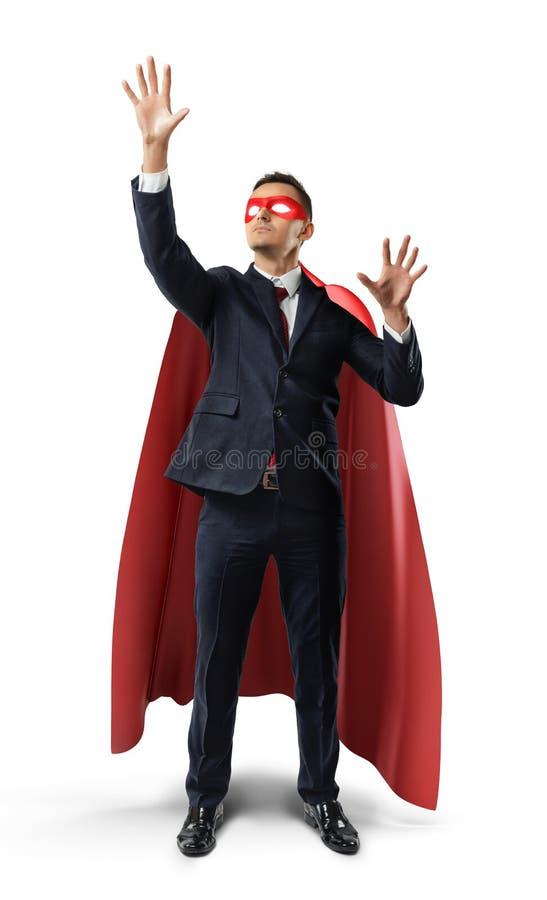 Ein Geschäftsmann in einem Gesellschaftsanzug- und Superheldkap unsichtbaren digitalen Schirm manipulierend wendet ein stockfotos