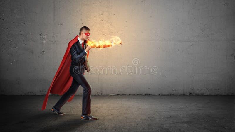 Ein Geschäftsmann in einem roten Superheldkap und lodernde Handwerfende Durchschläge an einem unsichtbaren Feind auf konkretem Hi lizenzfreie stockbilder