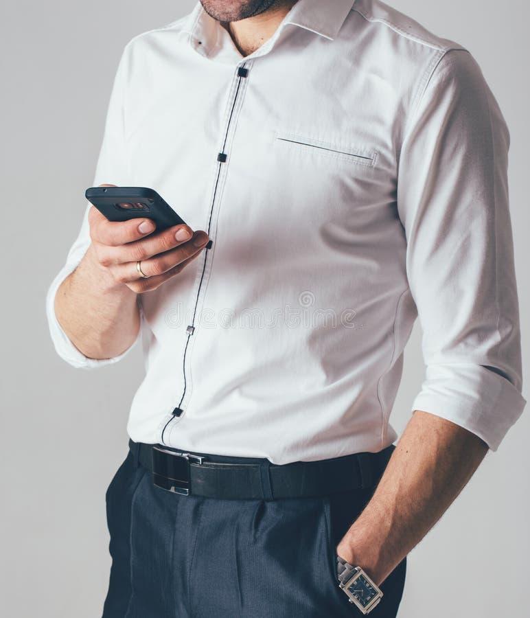 Ein Geschäftsmann in einem weißen Hemd und in schwarzen Hosen hält ein Telefon in seiner Hand im Büro Ein Mann trägt eine Armband lizenzfreies stockbild