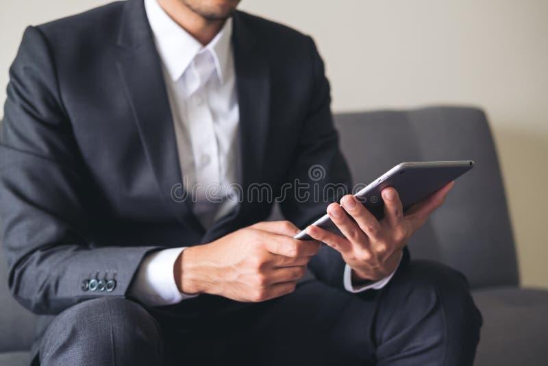Ein Geschäftsmann in einer grauen Klage, die auf Sofaholding sitzt, Tabletten-PC nach Arbeit verwendet und betrachtet lizenzfreie stockbilder