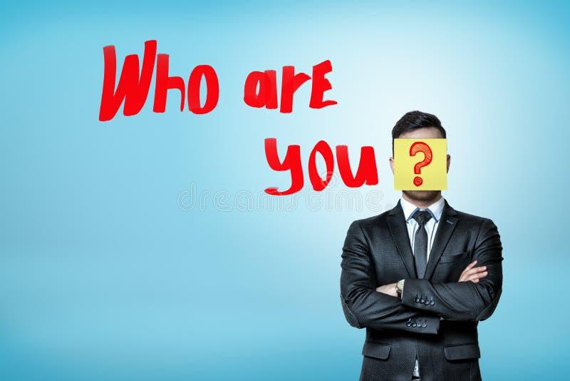 Ein Geschäftsmann in einer intelligenten Klage, Gesicht versteckt hinter einer gelben Aufkleberanmerkung mit einem Fragezeichen a stock abbildung