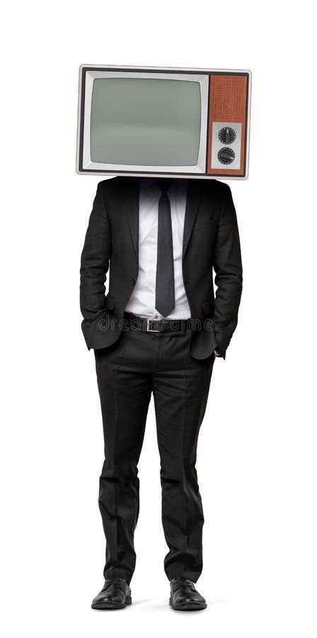 Ein Geschäftsmann im einem lokalisierten Hintergrund mit den Händen in seinen Taschen und einem alten Fernsehen anstelle seines K stockfoto