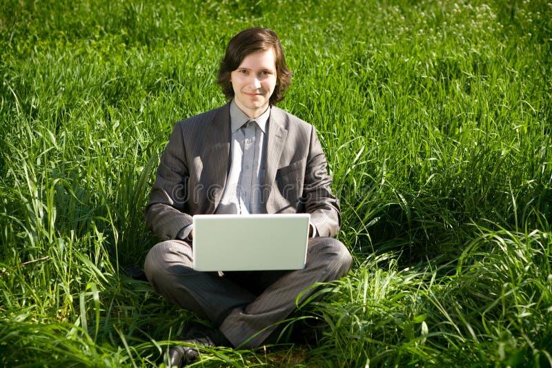 Ein Geschäftsmann mit einem Laptop auf dem Grasfeld lizenzfreie stockbilder