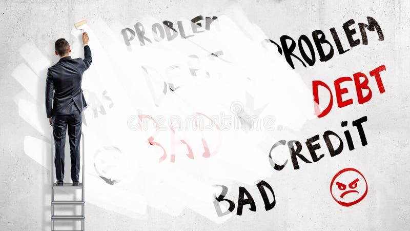 Ein Geschäftsmann steht auf einem Bockleiter und Farben über Wörter Problem, Schuld und Kredit mit einer weißen Farbenrolle lizenzfreie stockfotos