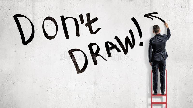 Ein Geschäftsmann steht auf einer roten Leiter und macht einen schreibenden Don-` t abgehobenen Betrag auf einer schwarzen Wand lizenzfreies stockbild