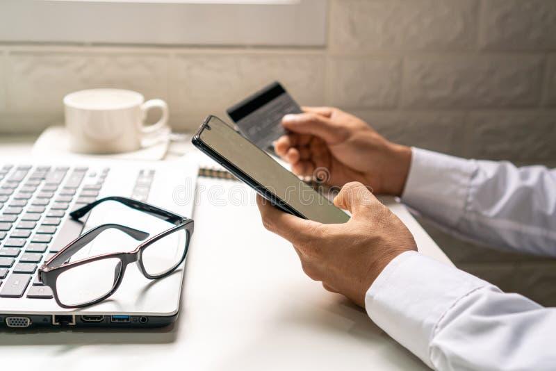Ein Geschäftsmann unter Verwendung der beweglichen intelligenten Telefon- und haltenkreditkarte für online kaufen lizenzfreie stockbilder