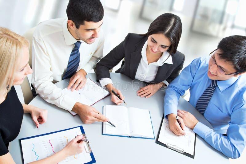 Ein Geschäftsteam der Arbeit mit vier Plänen stockbild