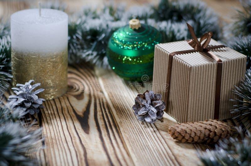 Ein Geschenk legt auf einen Holztisch nahe bei einer Kerze, Kegeln und einem Engel vor dem hintergrund der Weihnachtsdekorationen lizenzfreie stockbilder