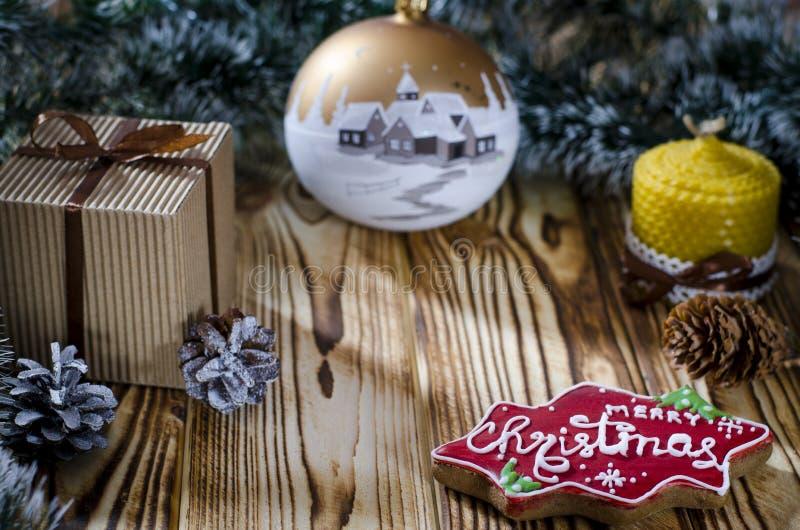 Ein Geschenk legt auf einen Holztisch nahe bei einer Kerze, Kegeln und einem Engel vor dem hintergrund der Weihnachtsdekorationen lizenzfreies stockbild