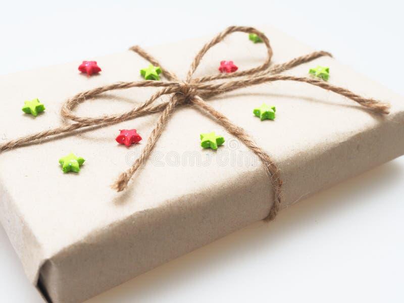 Ein Geschenk oder eine Geschenkbox eingewickelt durch raues braunes Recyclingpapier und mit braunem Hanfseil als Band mit Rot- un stockfoto
