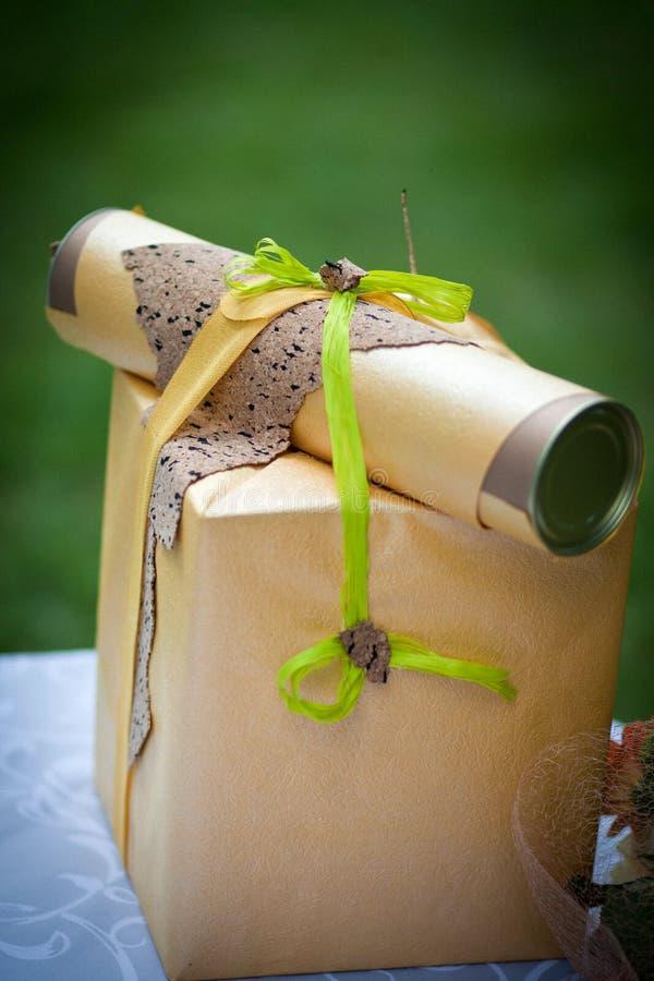 Ein Geschenk verpackt in einer Geschenkbox mit einem Glückwunschbrief lizenzfreies stockfoto