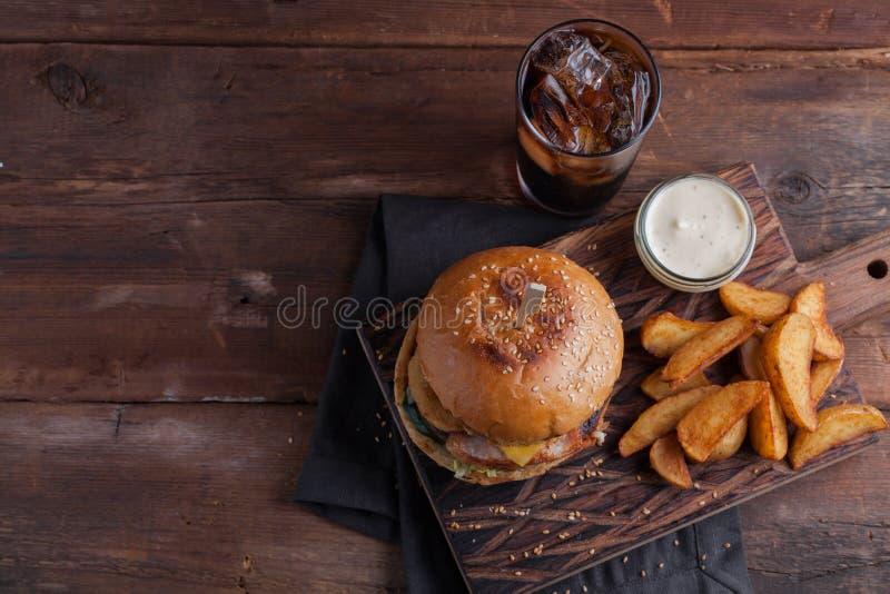 Ein geschmackvoller Burger mit Snäcken in Form von Kartoffeln mit weißer Knoblauchsoße und einem Glas kaltem Kolabaum saftiger Bu lizenzfreies stockbild