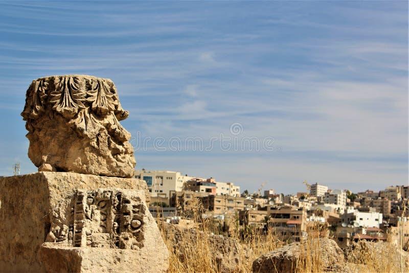 Ein Gesicht schnitzte auf einem Stein mit dem Hintergrund der Stadt von Jerash lizenzfreies stockfoto