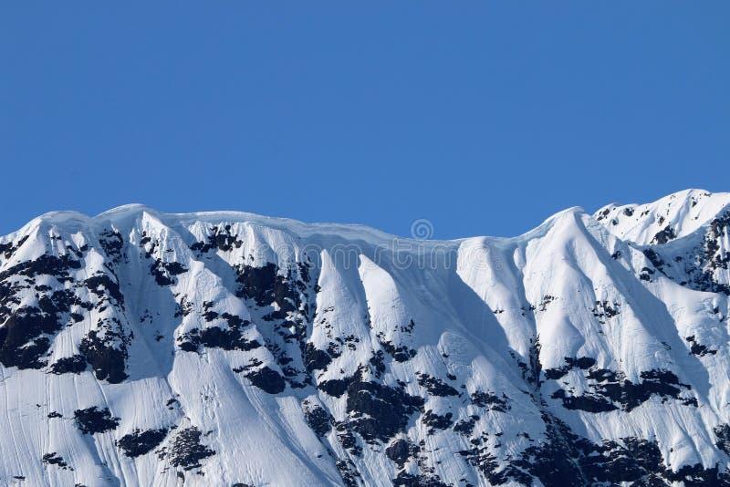 Ein Gesims auf Schnee bedeckte Kante in Alaska mit einer Kappe stockfotos