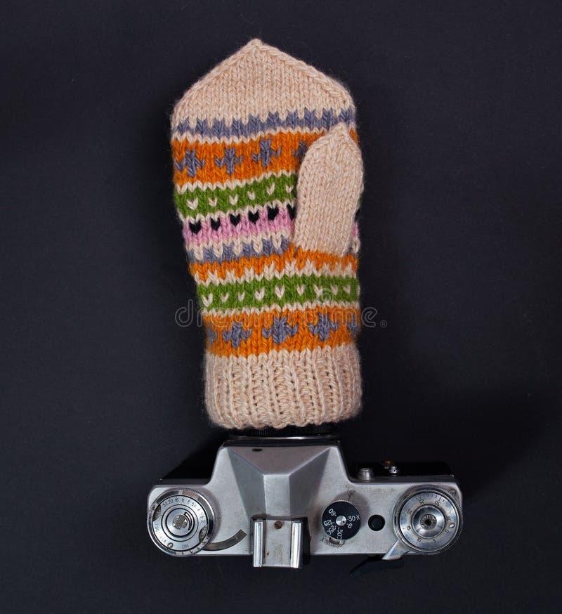 Ein gestrickter Handschuh wird auf einem WeinleseKameraobjektiv getragen Beschneidungspfad eingeschlossen stockfotografie