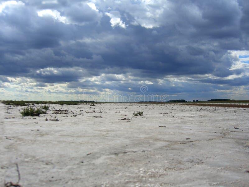 Ein getrocknetes-oben Flussbett der Salzseewüste die nackte Unterseite des Reservoirs in Kasachstan mit Sturmwolken-Naturlandscha stockbild