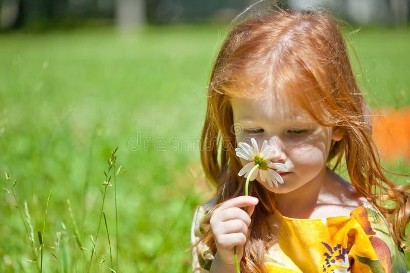 Ein ginger-haired Mädchen mit einer Blume lizenzfreie stockfotos