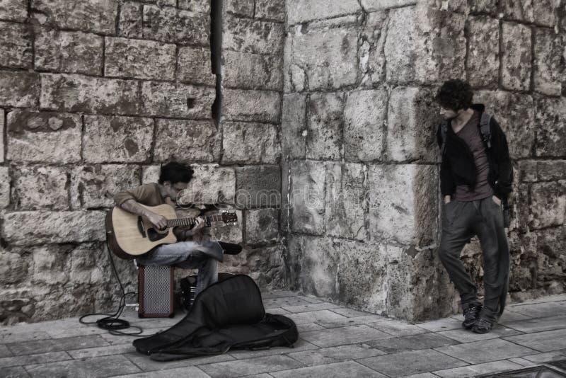 Ein Gitarrist spielt in der Straße, während Leute hören stockfoto