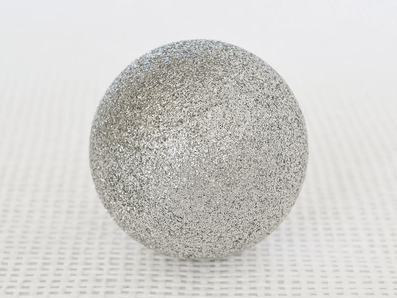 Ein glänzender silberner Weihnachtsball mit Scheinen auf einem weißen strukturellen Hintergrund stockfoto
