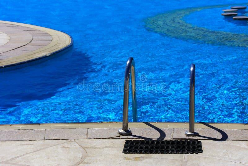 Ein glänzendes Treppenhaus wird in das schöne Pool gesenkt stockfotos
