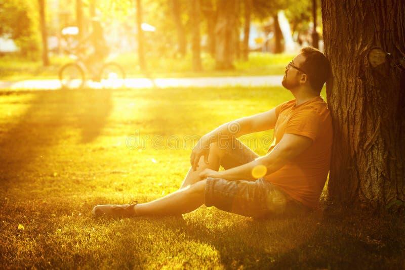 Ein glücklicher durchdachter Träumermann sitzt auf grünem Gras im Park stockfoto