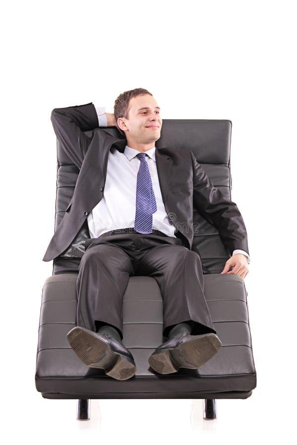 Ein glücklicher Geschäftsmann, der einen Rest auf einem Sofa nimmt lizenzfreies stockbild