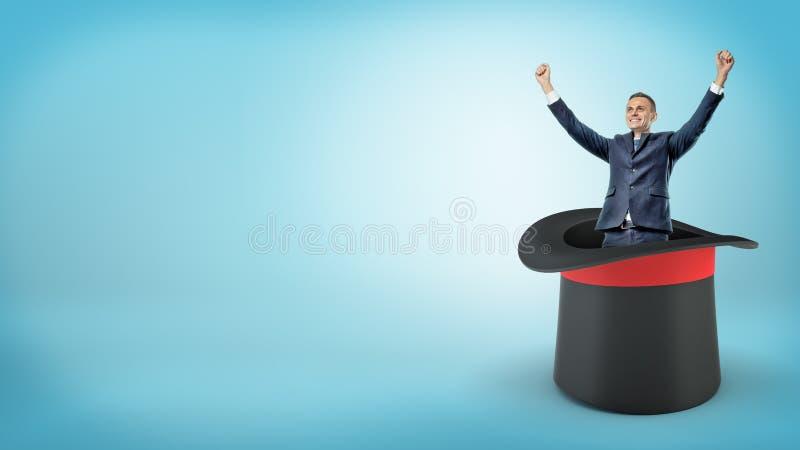 Ein glücklicher Geschäftsmann mit den angehobenen Armen steht in einem enormen schwarzen Zauberkünstlerhut auf blauem Hintergrund stockbilder