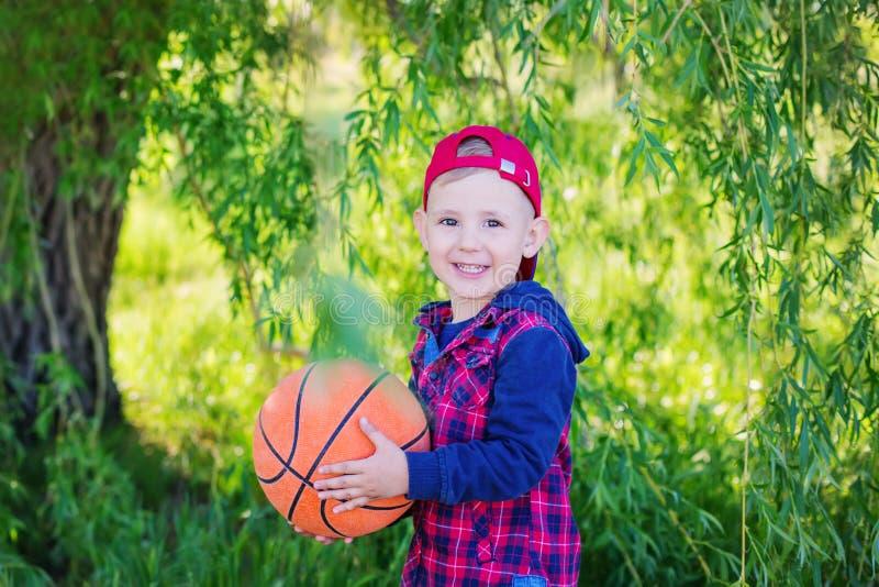Ein glücklicher Junge, der einen Basketball übergibt stockfotografie