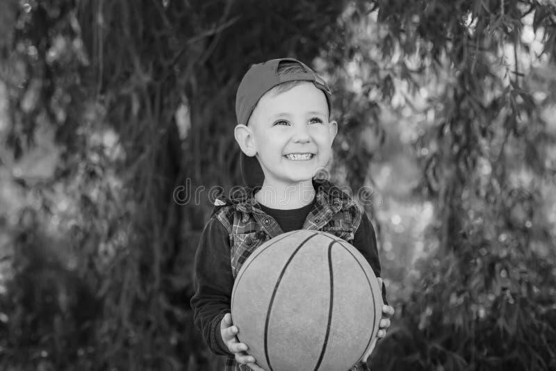 Ein glücklicher Junge, der einen Basketball übergibt lizenzfreies stockbild