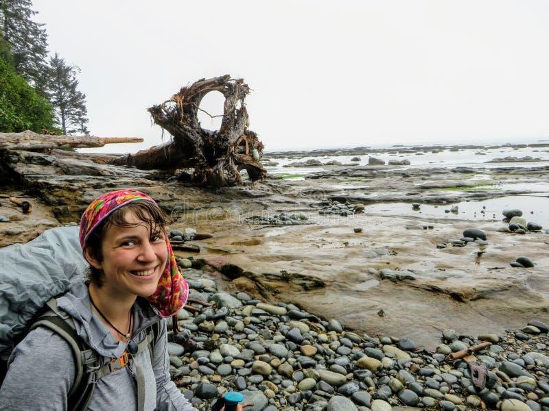 Ein glücklicher junger weiblicher Wanderer, der nass Stellung auf dem felsigen Ufer entlang der Westküsten-Spur, auf Vancouver Is stockfotos