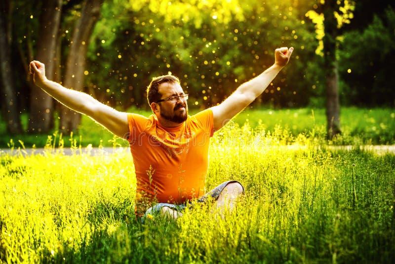 Ein glücklicher Mann ist auf grünem Gras mit squint Augen entspannend stockfotos