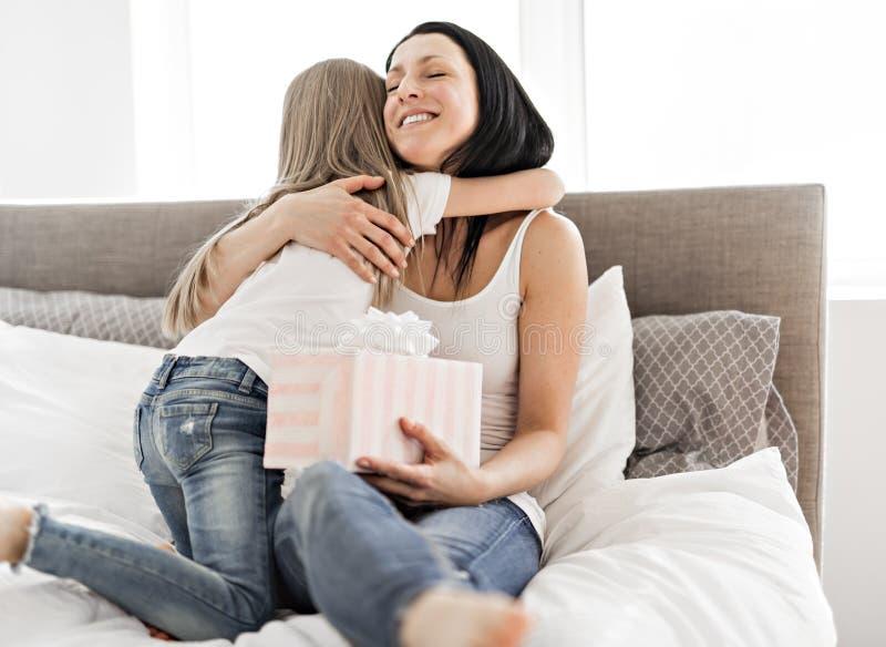 Ein glücklicher Muttertag Kindertochter beglückwünscht Mütter und gibt ihr ein Geschenk lizenzfreie stockfotografie