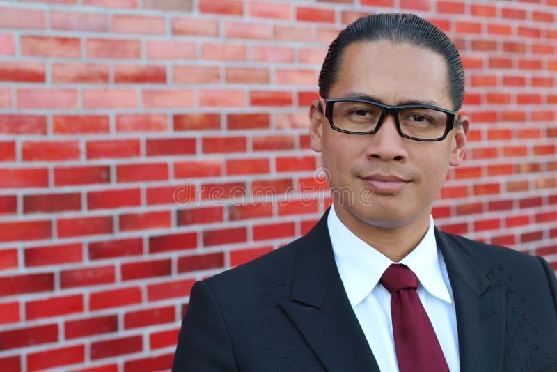 Ein glücklicher philippinischer Fachmann mit einem überzeugten Blick (auf einer Wand des roten Backsteins) lizenzfreie stockfotografie
