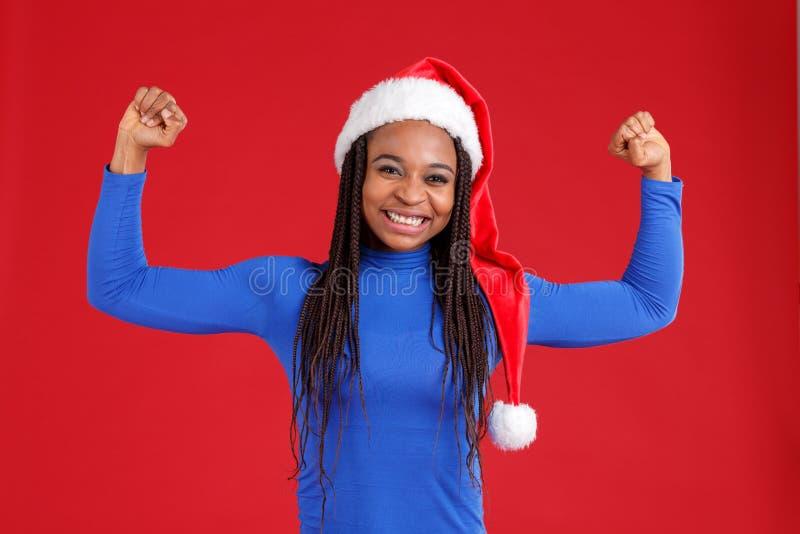 Ein glückliches Afroamerikanermädchen im blauen Golf und in einem Weihnachtshut zeigt das Bizeps ihrer Hände und lächelt stockfotografie