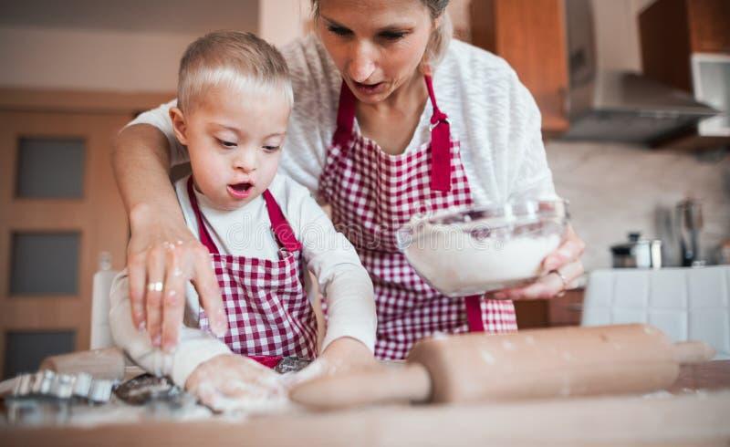 Ein glückliches behindertes Down-Syndrom Kind mit seiner zuhause backenden Mutter lizenzfreies stockfoto