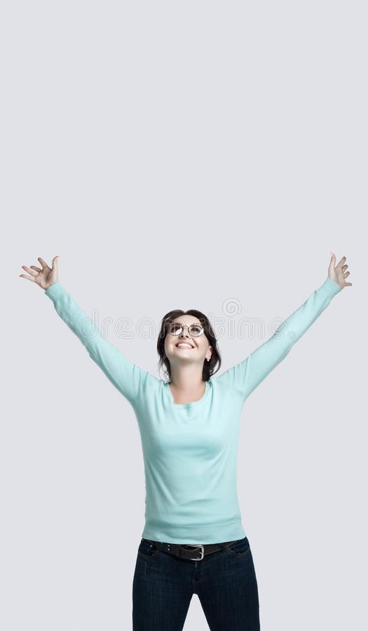 Ein glückliches brunette Mädchen in einem Minze-farbigen Pullover steht gegen den grauen Hintergrund, den die junge Frau ihre Hän lizenzfreies stockbild