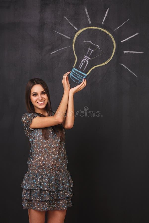 Ein glückliches junges Mädchen hat eine großartige Idee Eine Glühlampe auf der Tafel Das Konzept des Fanges die Idee lizenzfreie stockfotos