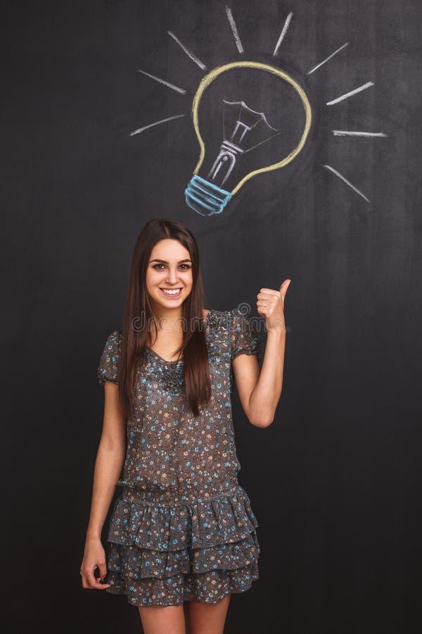 Ein glückliches junges Mädchen hat eine Idee Student zeigt ihren Finger auf die Glühlampe, die auf die Tafel gezeichnet wird lizenzfreie stockfotos
