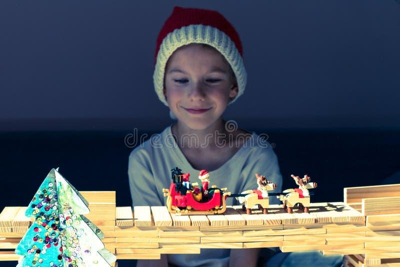 Ein glückliches Kind in Santa's-Hütte, die Sankt-` s Pferdeschlitten betrachtet lizenzfreie stockfotografie