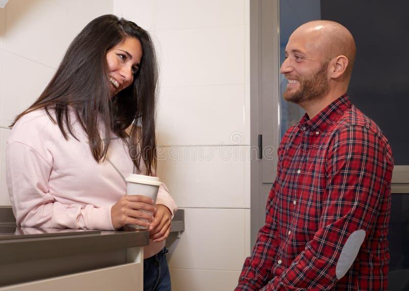 Ein glückliches Paar, das in der Küche lächelt stockfotografie