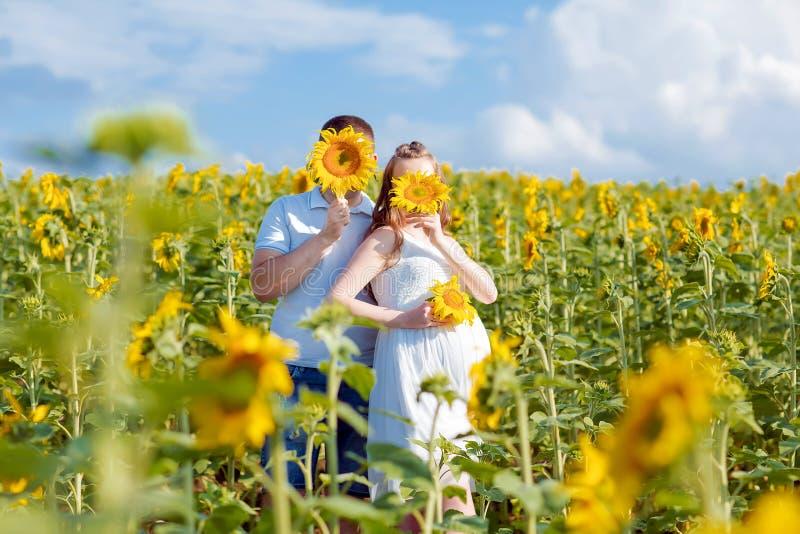 Ein glückliches Paar, das Zeit in der Landschaft genießt Mann und Frau, die auf Sonnenblumenfeld lächeln und stillstehen Schwange stockfotografie