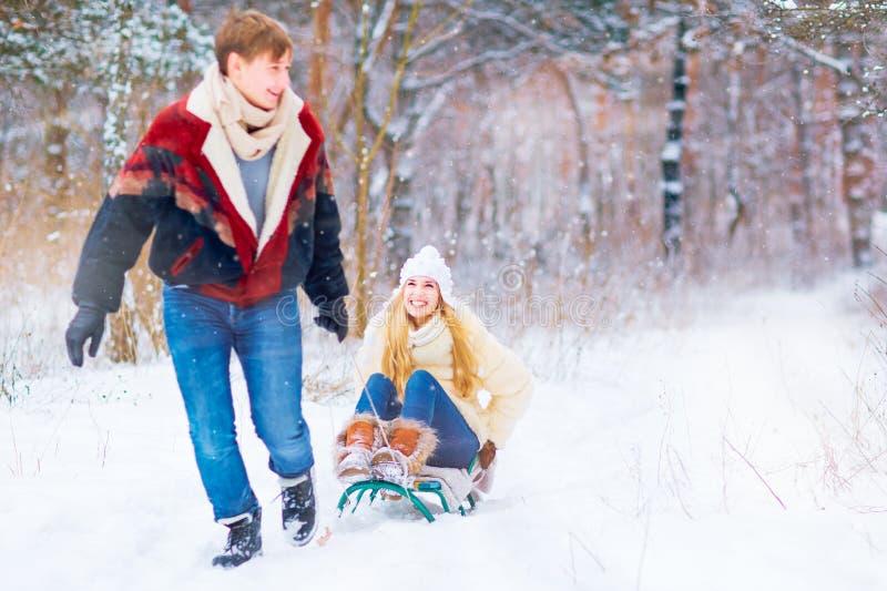 Ein glückliches Paar reitet einen Schlitten im Schnee in einem Park im Gewinn stockbilder