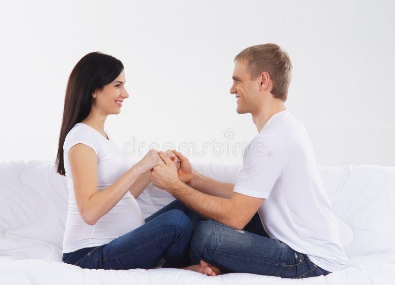 Ein glückliches Paar, welches auf das Baby in der weißen Kleidung wartet stockbild