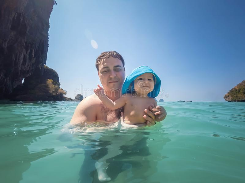 Ein gl?ckliches Baby von sieben Monaten badet im Meer zum ersten Mal Sonniger Tag, Vati h?lt das Baby lizenzfreies stockbild