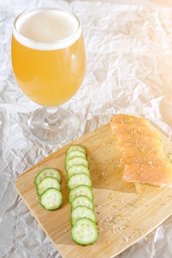 Ein Glas Bier und frische Fische und geschnittene Gurken auf einem hölzernen Stand am sonnigen Tag lizenzfreie stockfotografie