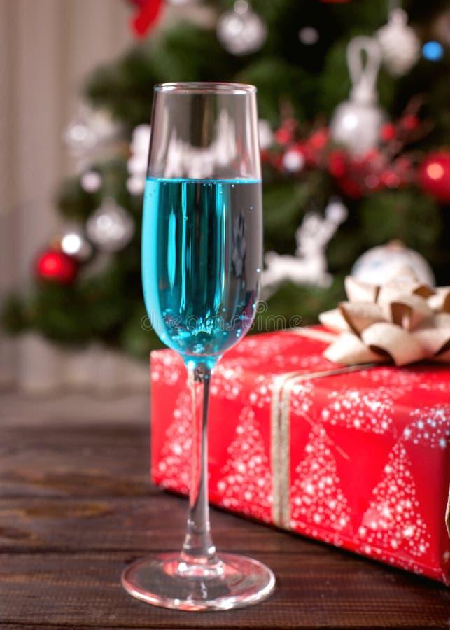 Ein Glas blauer Champagner auf dem Hintergrund eines Weihnachtsbaums stockbild