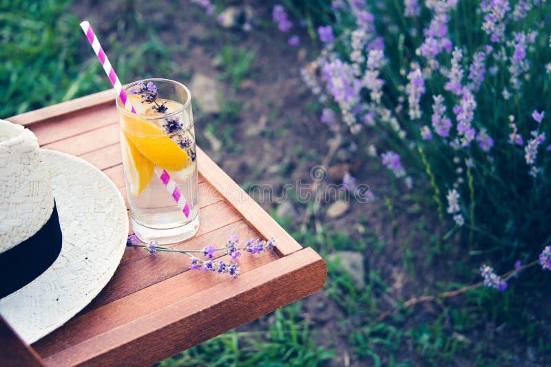 Ein Glas der Auffrischungslimonade und des Strohhutes über einem Holzstuhl Blühende Lavendelblumen im Hintergrund lizenzfreie stockfotos