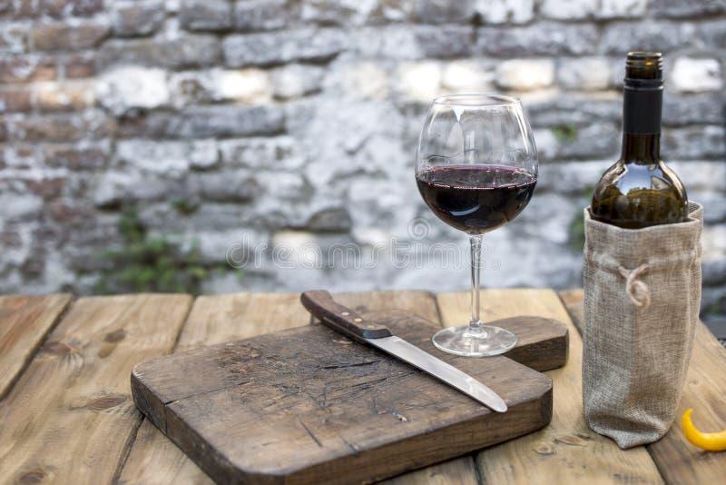 Ein Glas des Rotweins und der Flasche auf einem Holztisch und ein hölzernes altes Schneidebrett für Fleisch Kopieren Sie Platz stockfoto