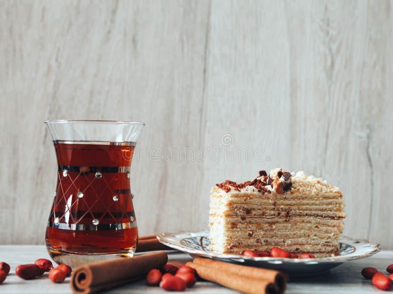Ein Glas des Tees, des Zimts und des Kuchens stockbilder