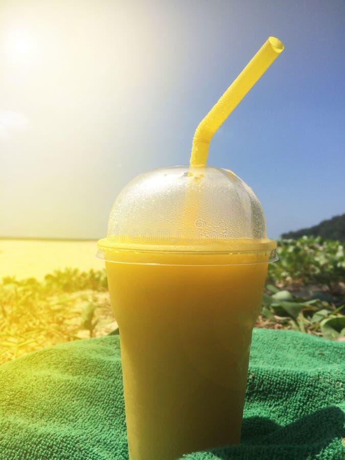 Ein Glas des tropischen kalten Cocktails des Sommers mit einem misted Deckel und einem Stroh steht auf dem Strand auf einem Tuch  stockfotografie